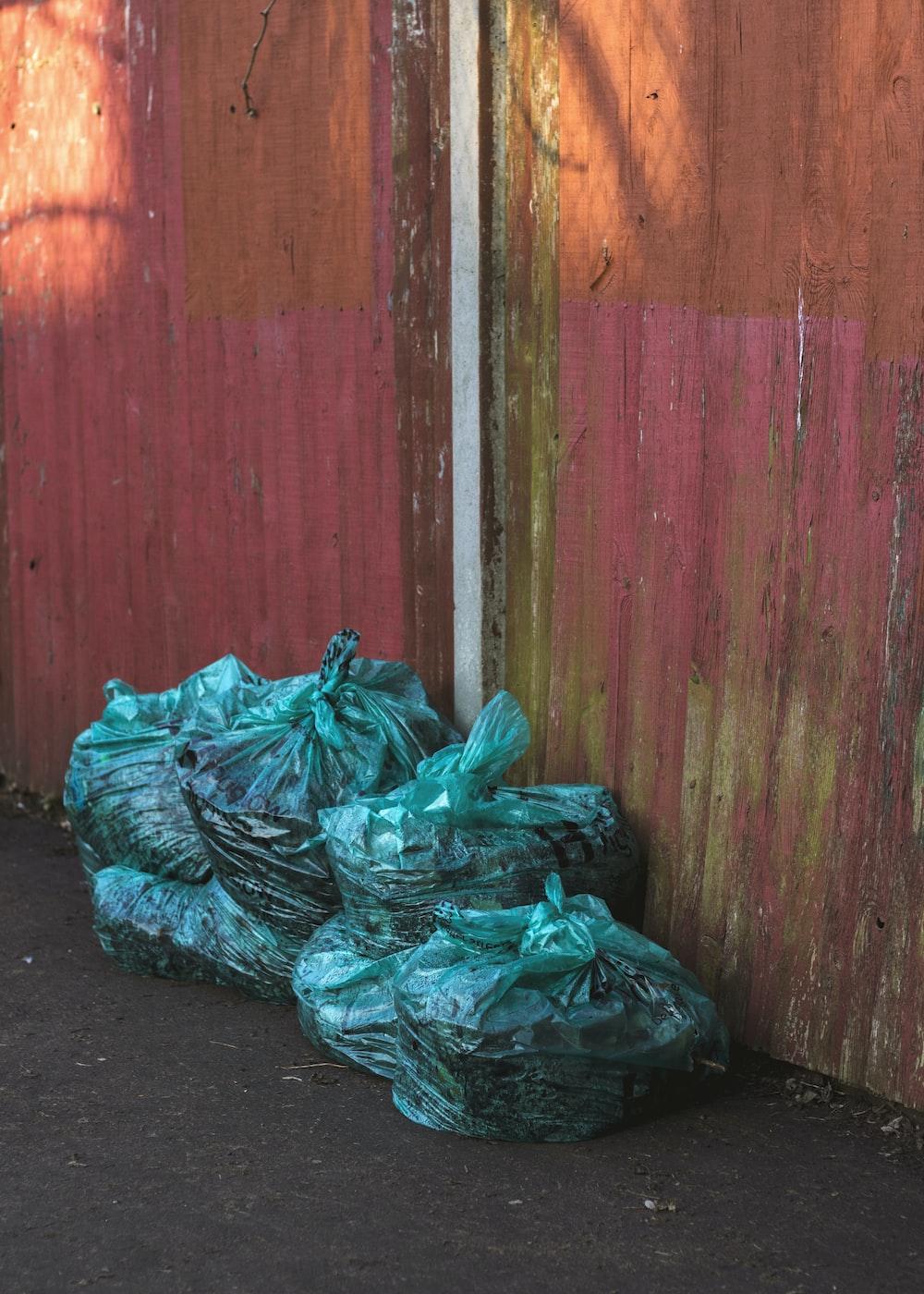 green plastic bags near wooden wall