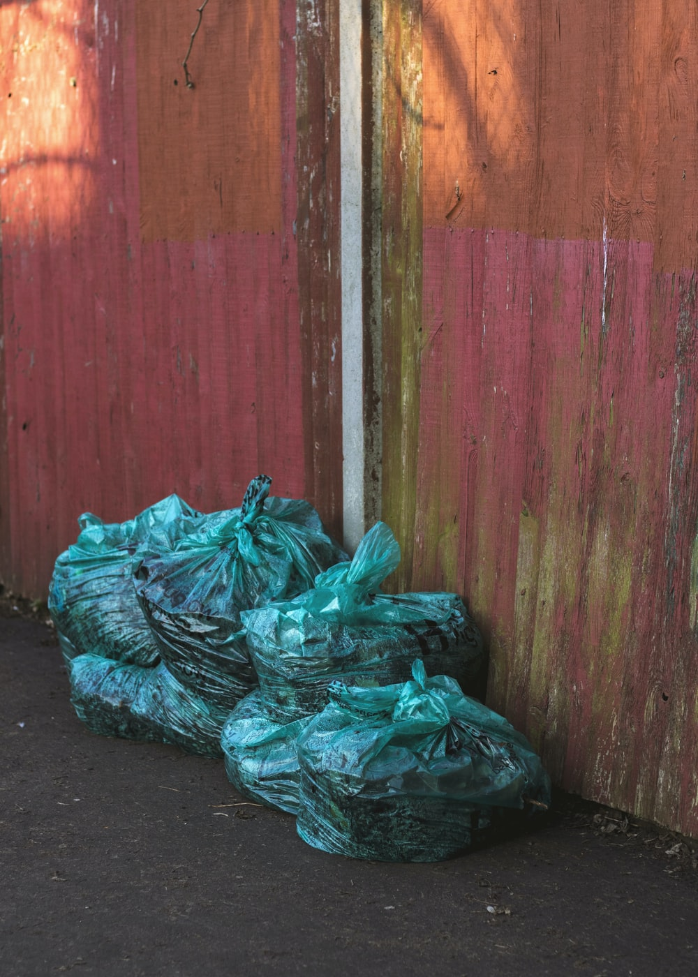 green plastic bags near wooden wall