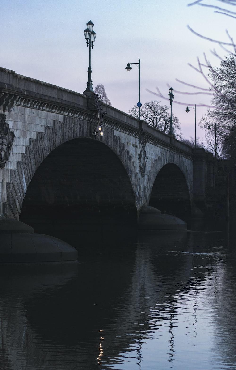 bridge over calm body of water under blue sky