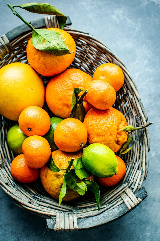 orange and lemon fruits on gray wicker basket