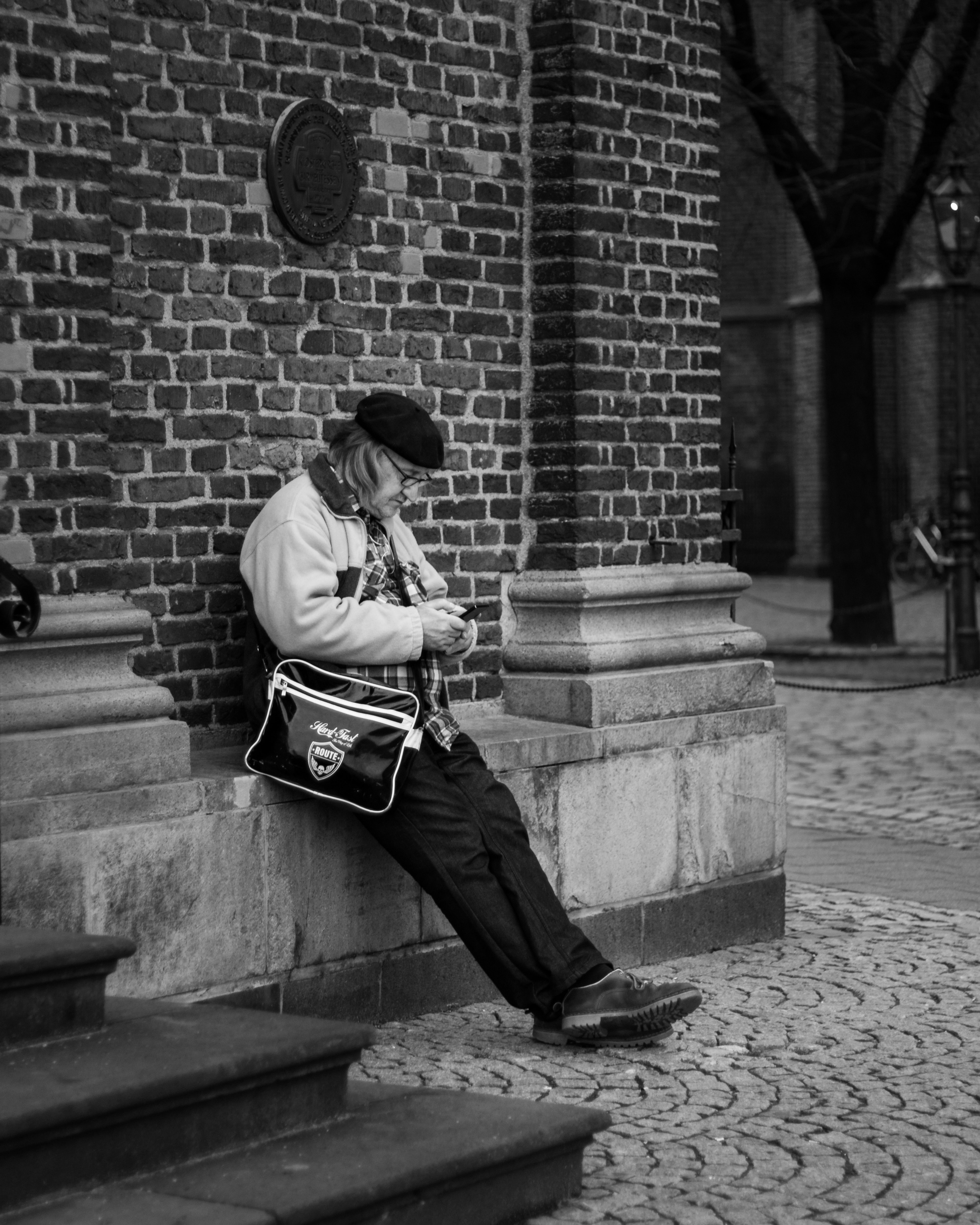 grayscale photography of man leaning on wall