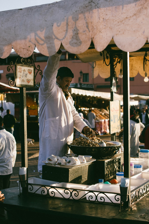 man in white shirt cooking on wok during daytime