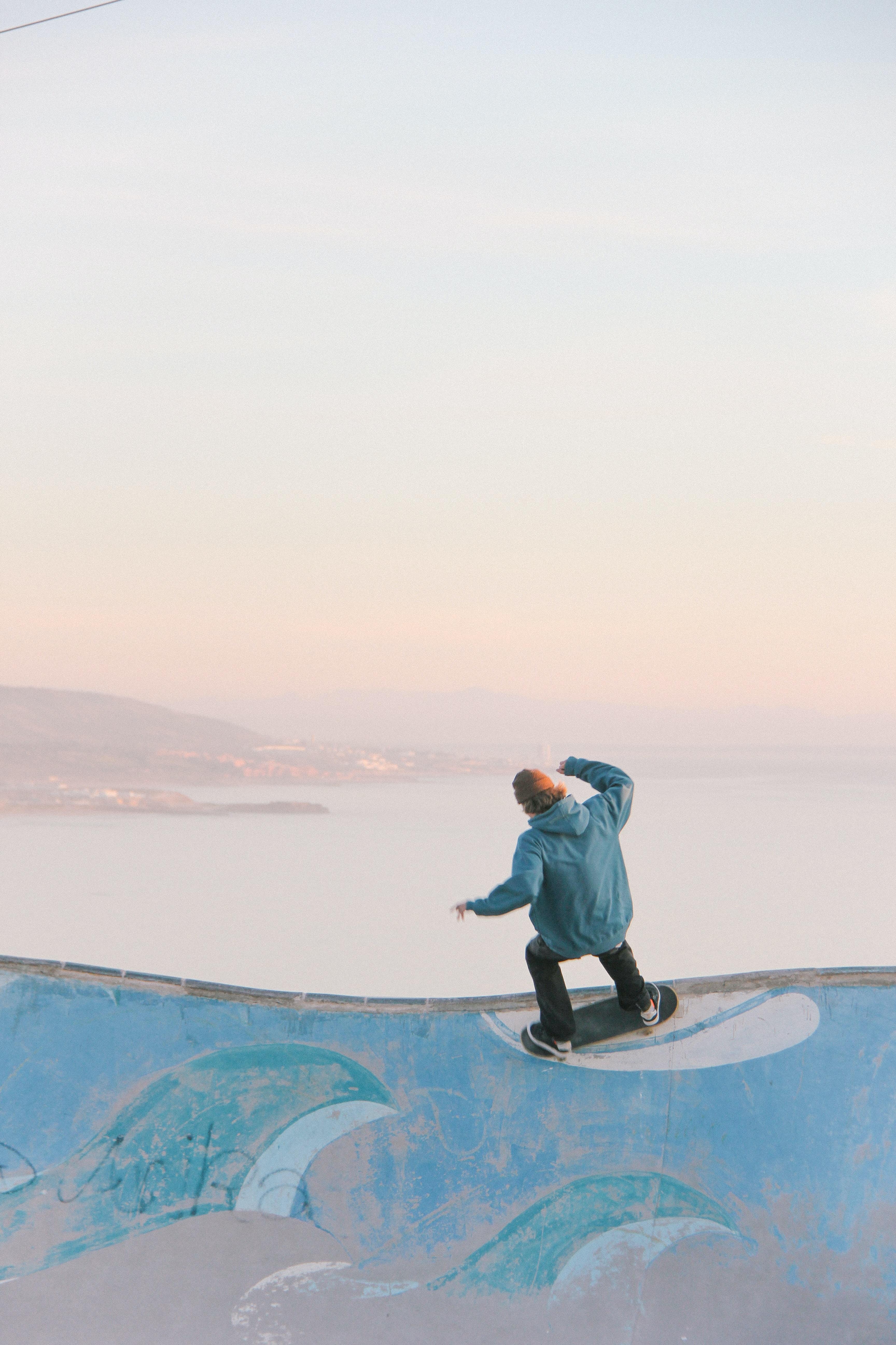 man in blue skateboarding on wall in beach