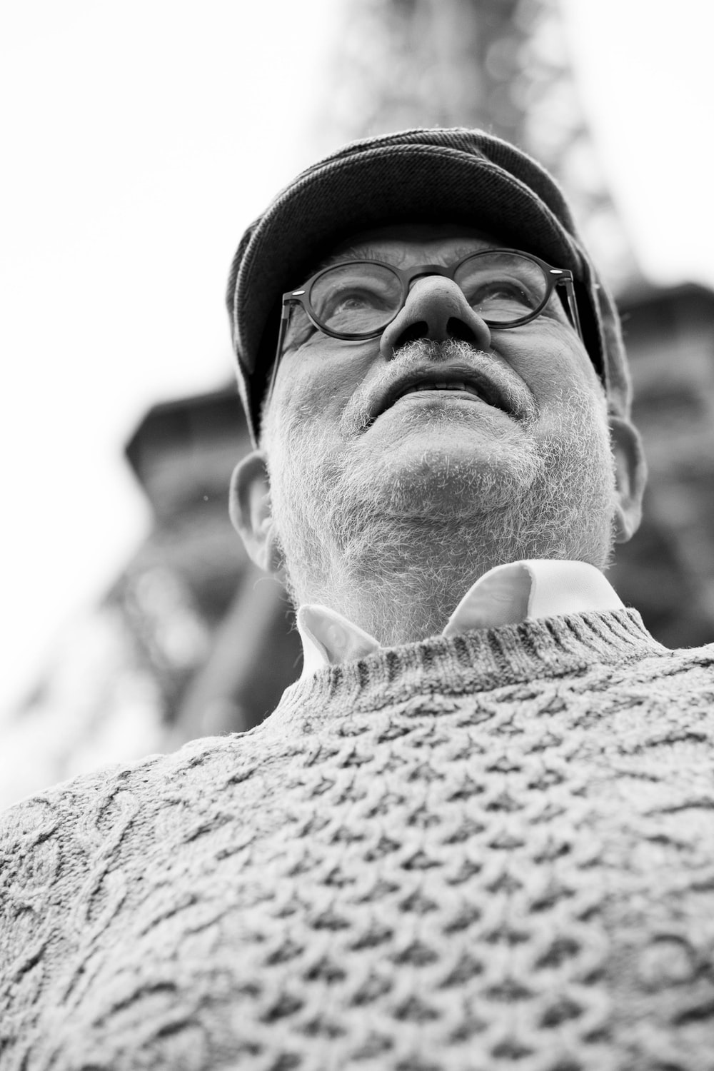 low angle view of man wearing hat and sweater under Eiffel Tower