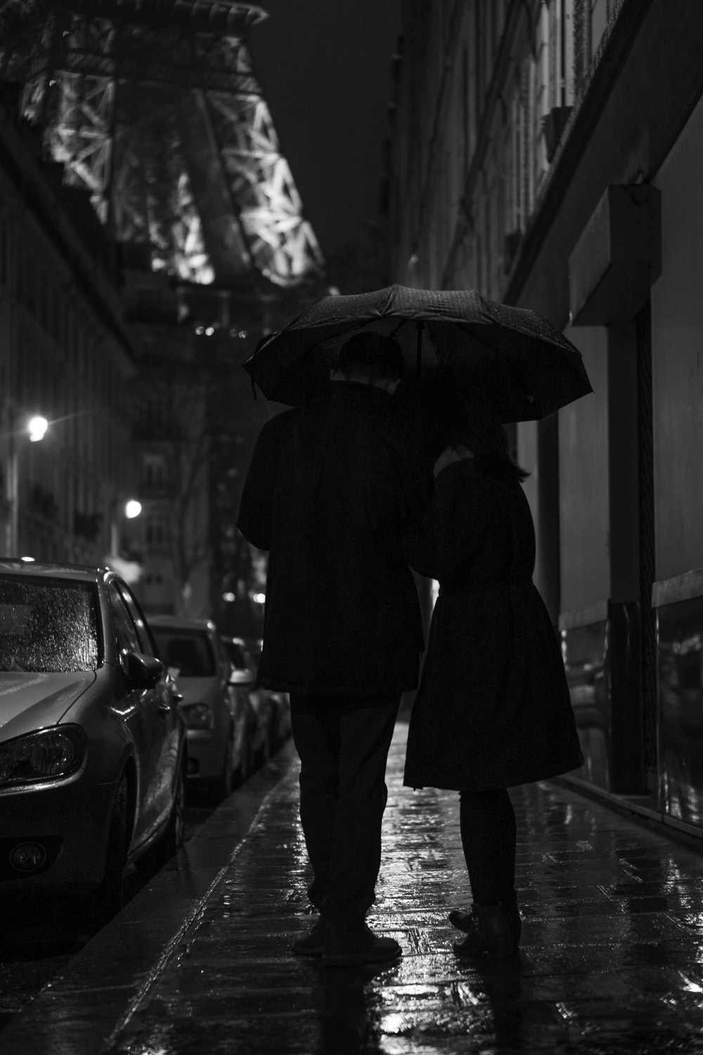 grayscale photography of man and woman standing under umbrella