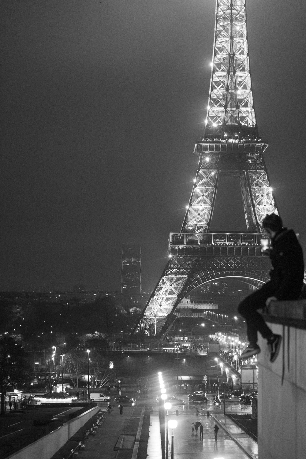 grayscale photo of man sitting on rooftop near Eiffel Tower, Paris