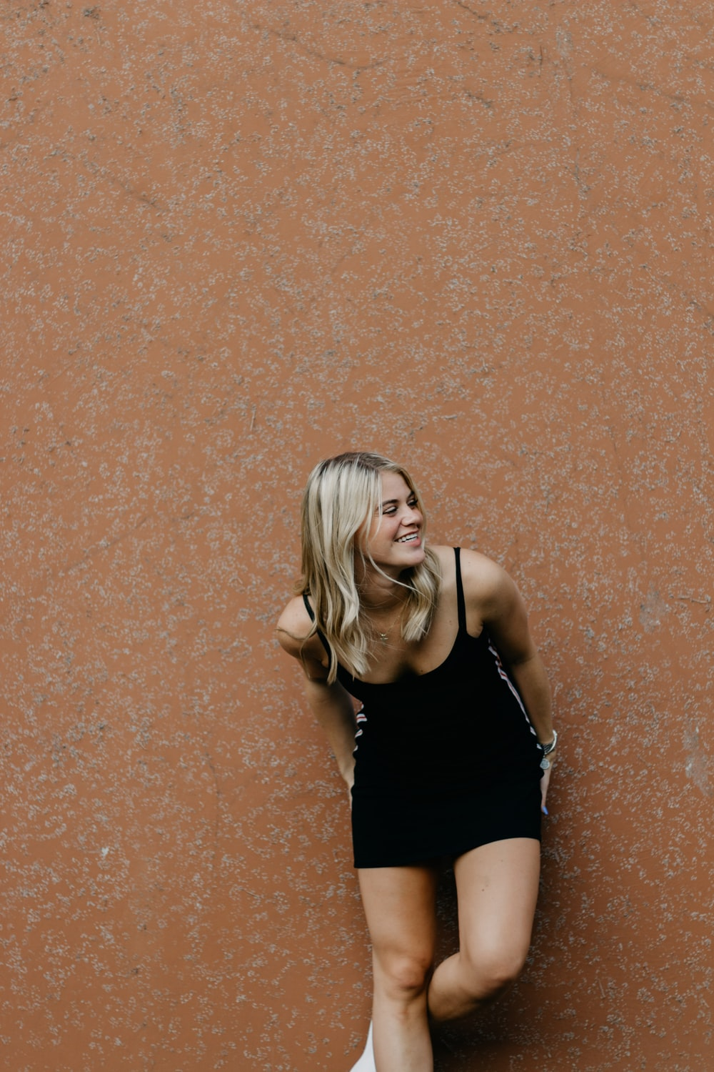 smiling woman leaning on brown wall