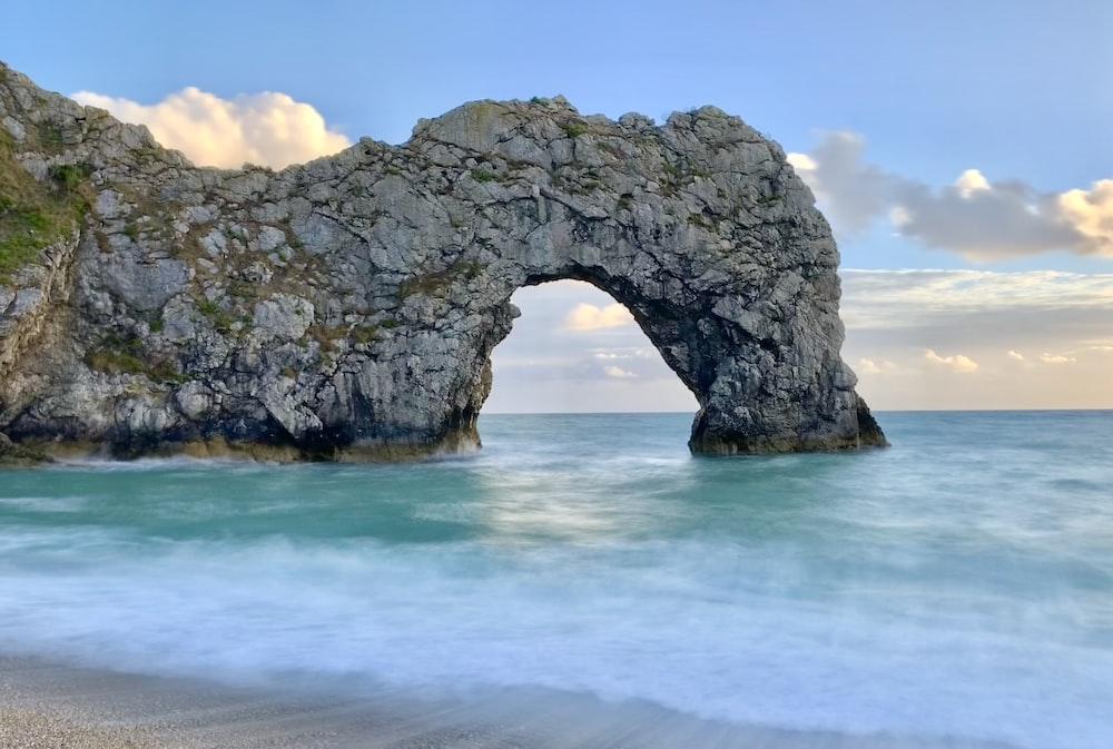 grey stone arc formation in beach