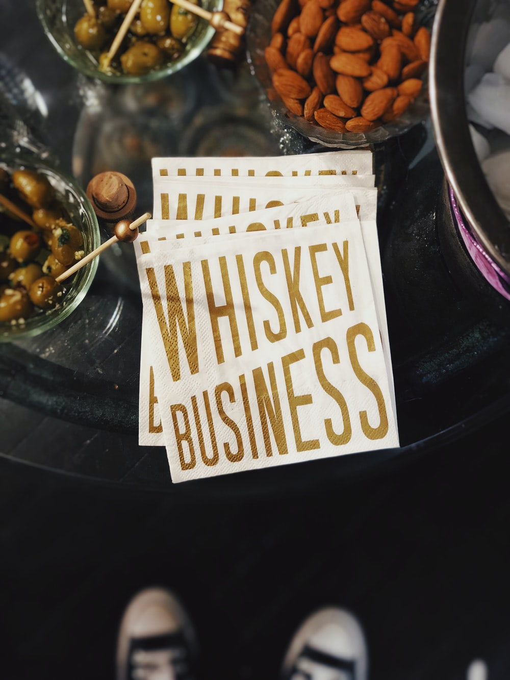 flat lay photo of almonds, green olives and whiskey signage