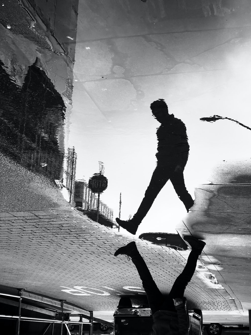 water reflection shadow of man walking on street in grayscale photography