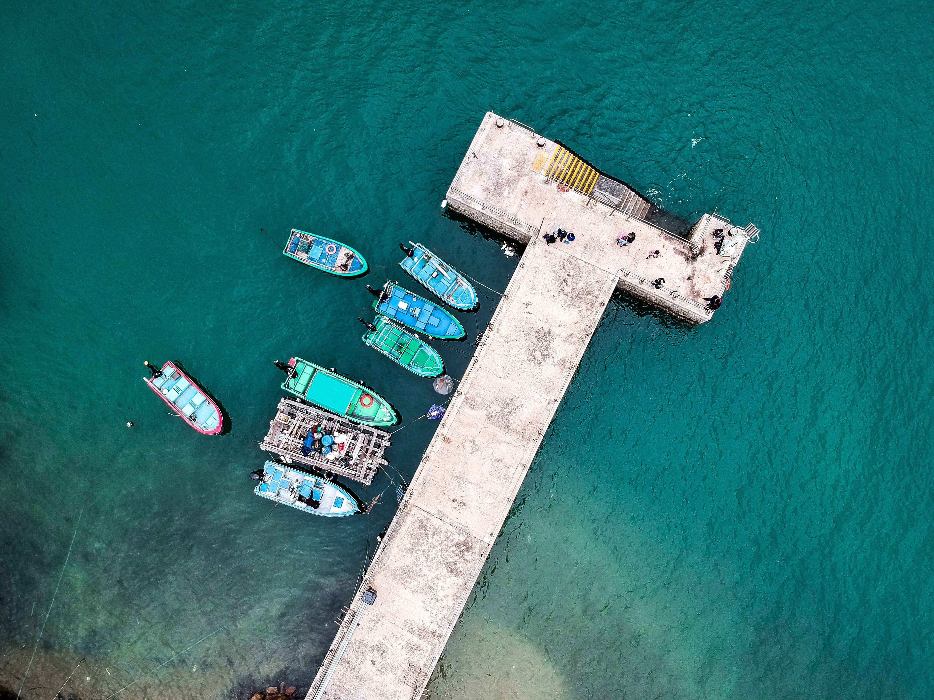 aerial photography of blue and green boats beside dock