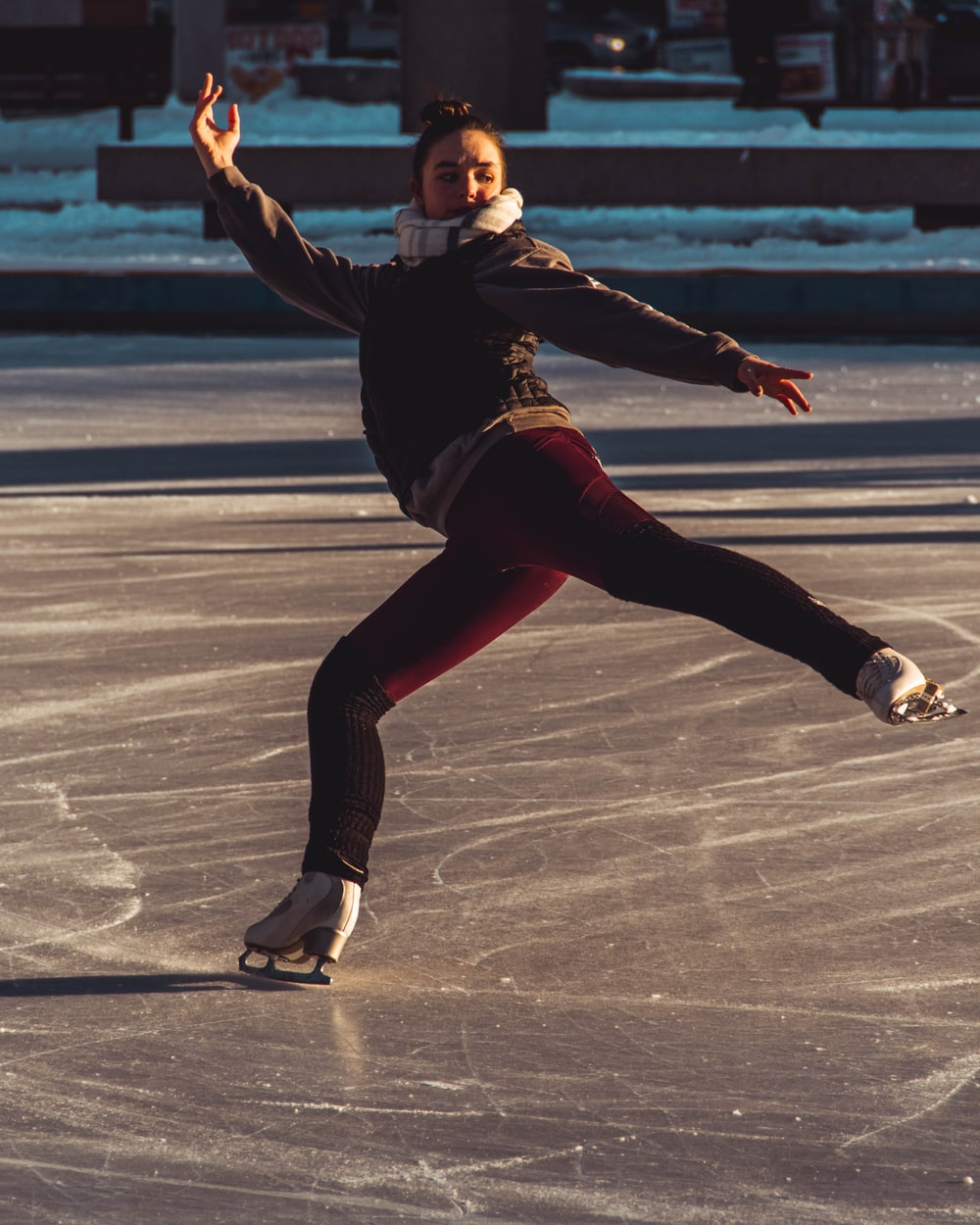 woman in red pants and coat using ice skates on skating rink