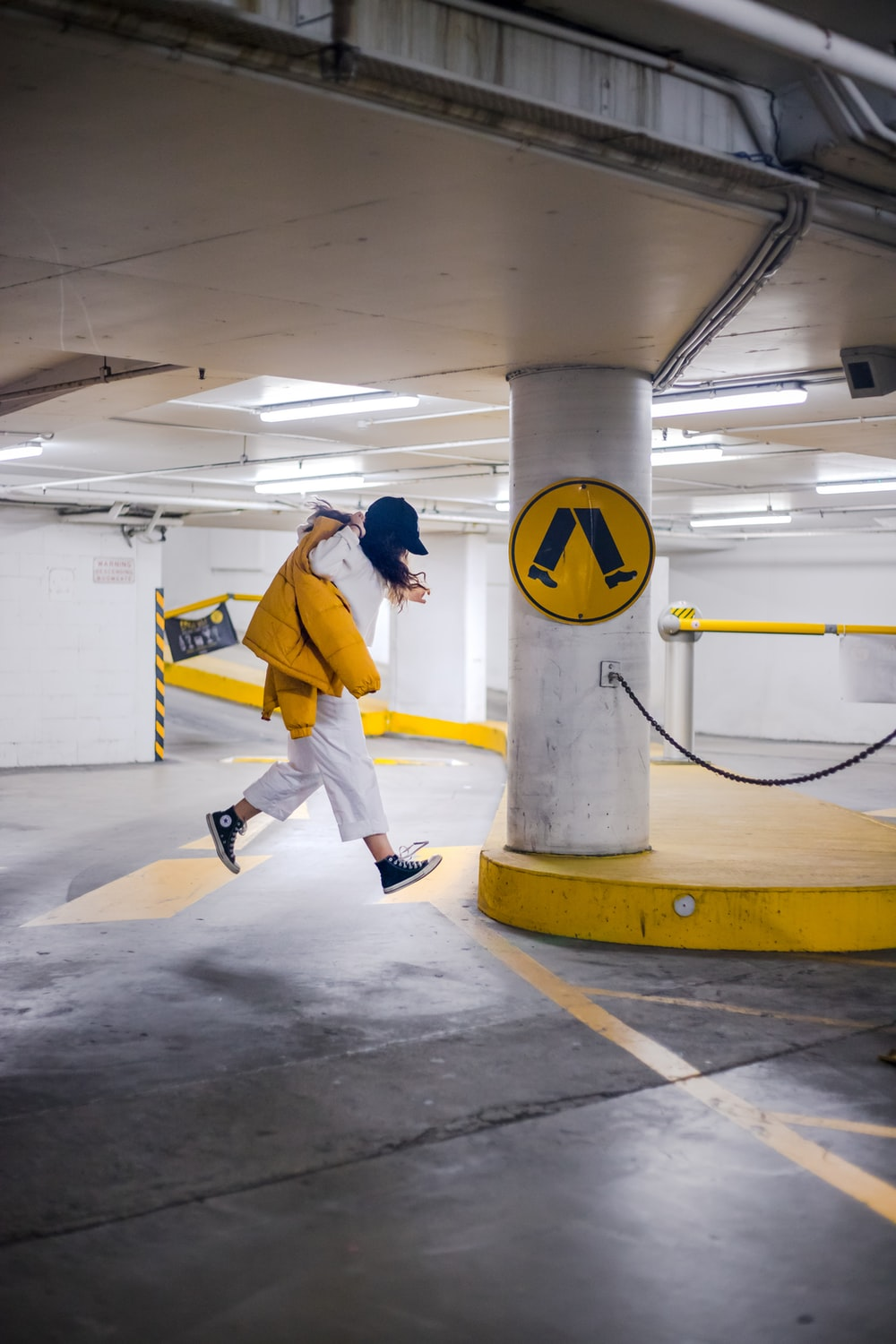 person wearing white jacket and pants jumping on parking lot