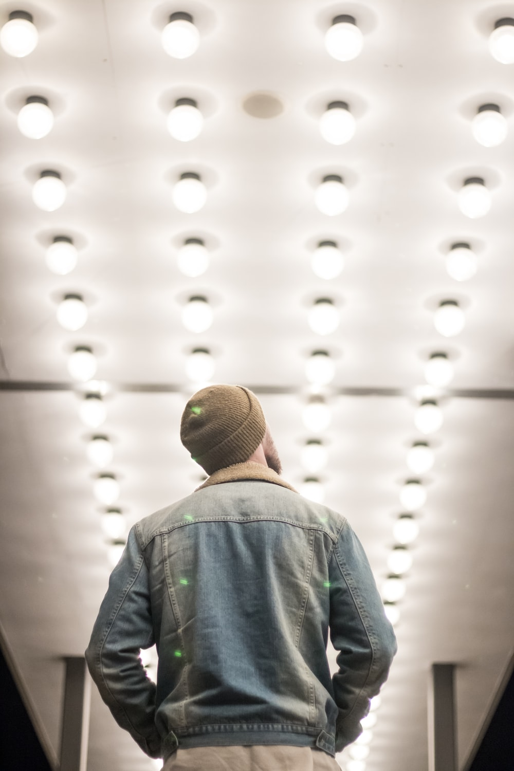 man in blue denim jacket standing on hall with lighted lights