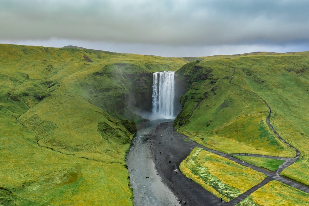 raging falls in between green and yellow grass covered mountains
