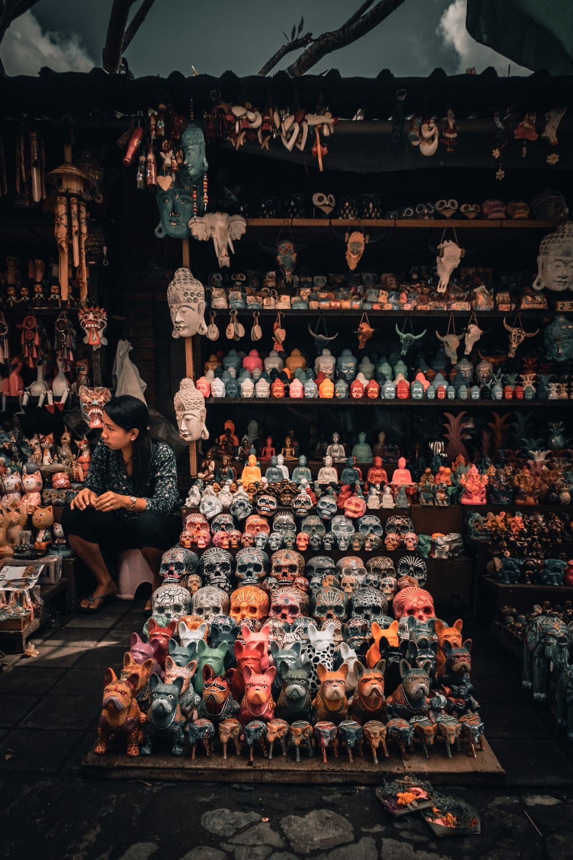 woman sits beside calavera figurine on display