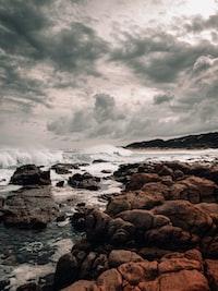 sea waves crashing on rocks under dramatic clouds