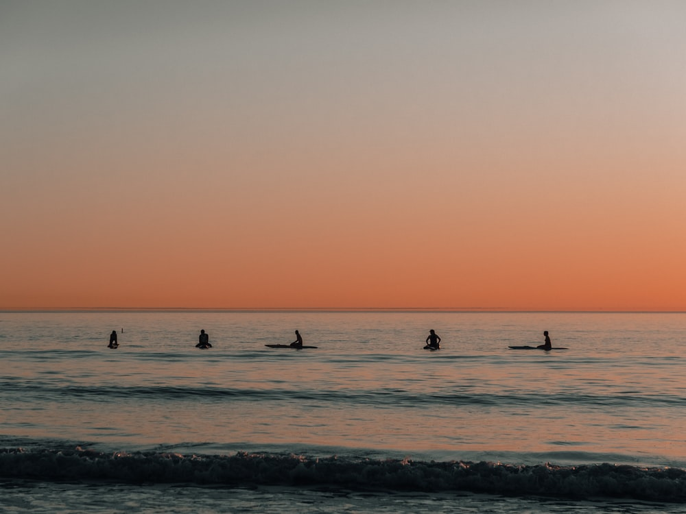 five people surfing on sea