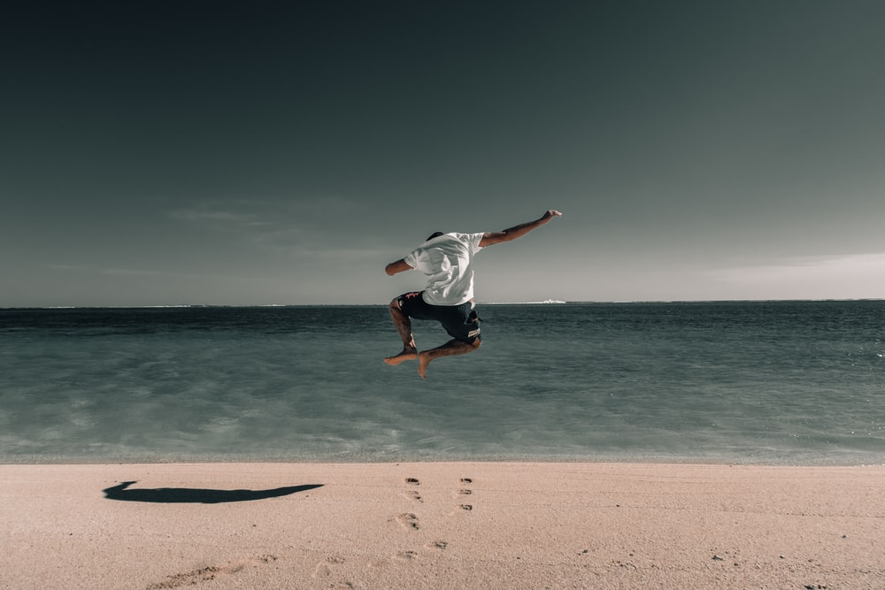 man suspended in air above beach sand