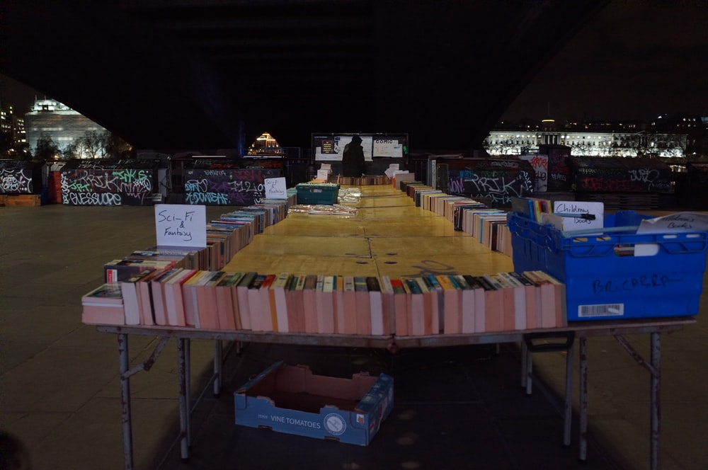 piled books on table beside boxes in store