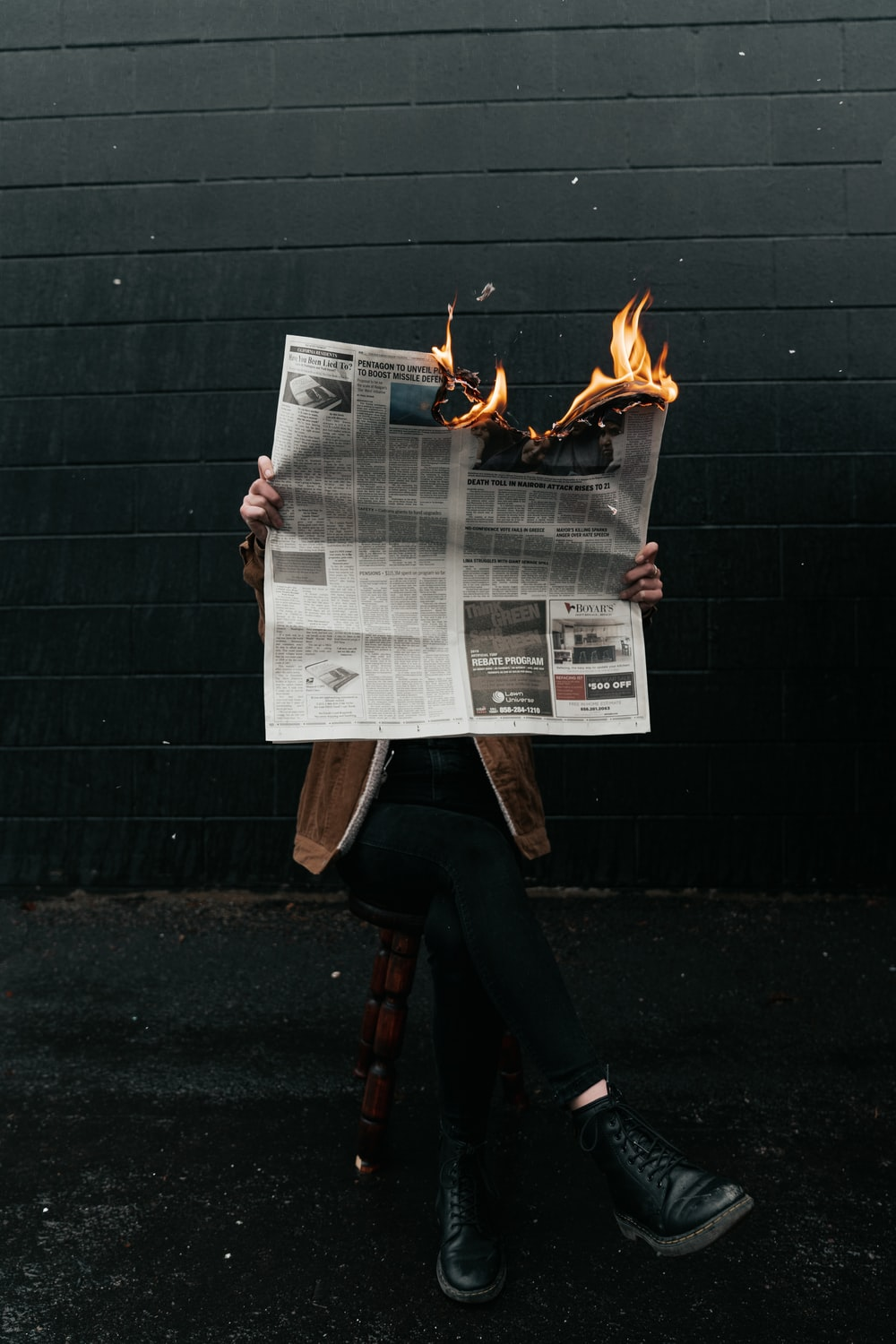 person reading with burning newspaper