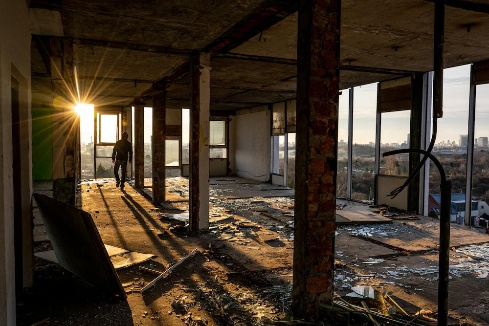 man walking inside broken building