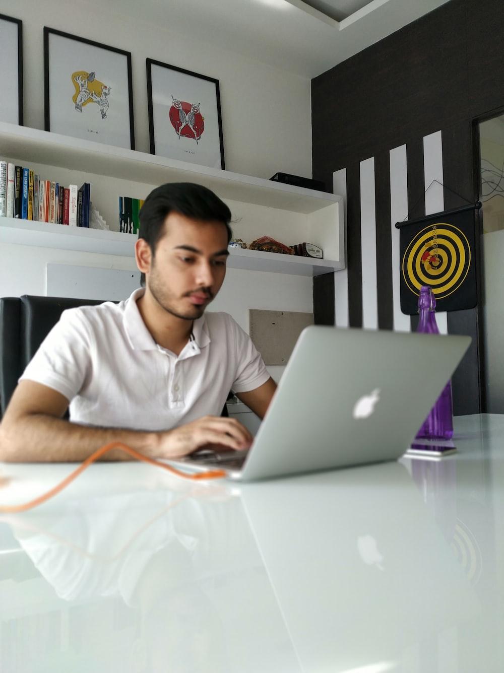 man using MacBook on table