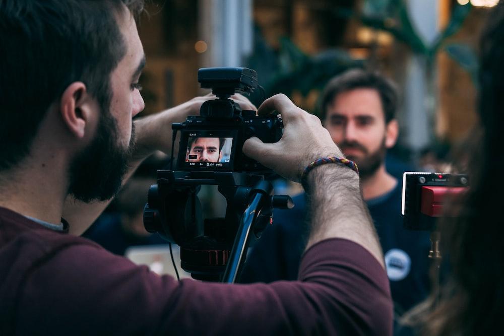 man taking video of standing man wearing black crew-neck top