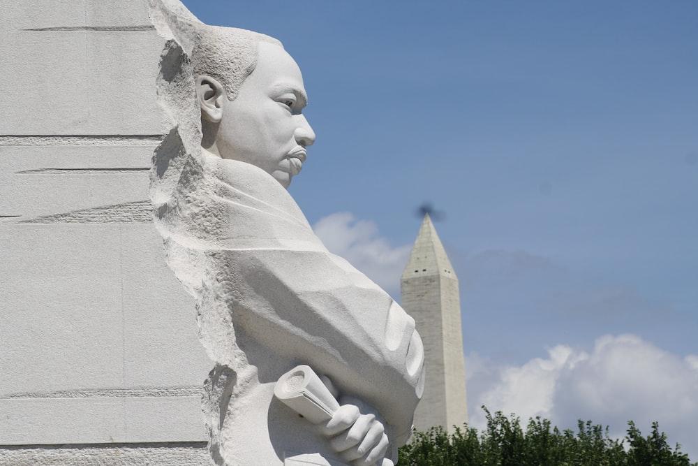 man's sculpture under blue sky