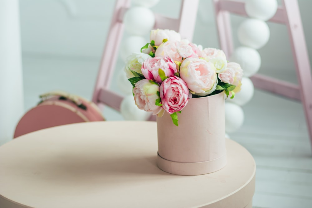 pink flowers in white vase on round table