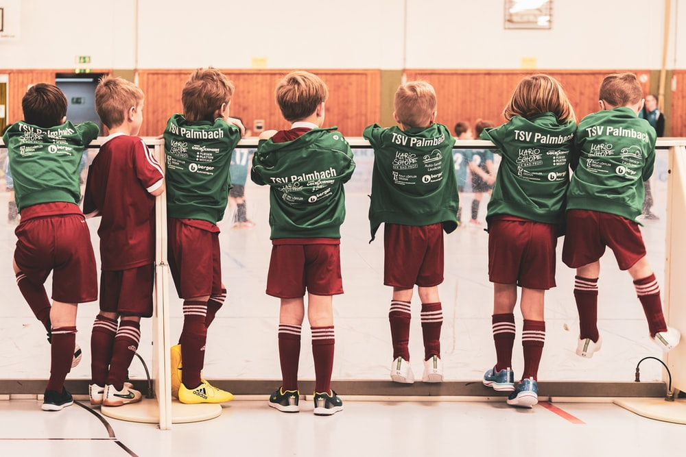 toddlers wearing sports jersey suit standing near white wall