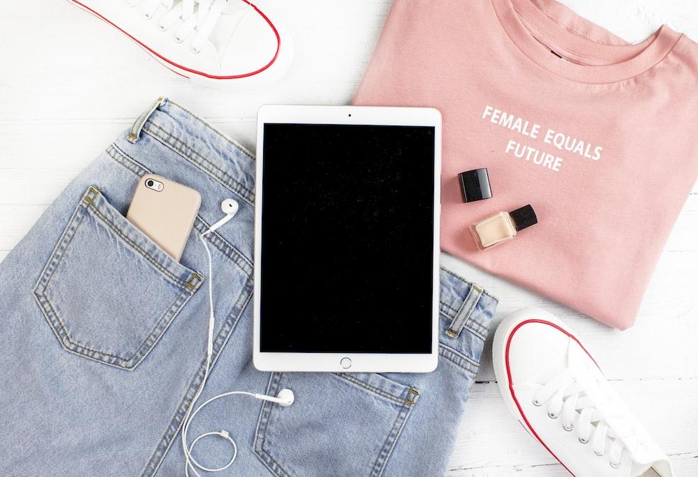 silver iPad on blue denim bottoms