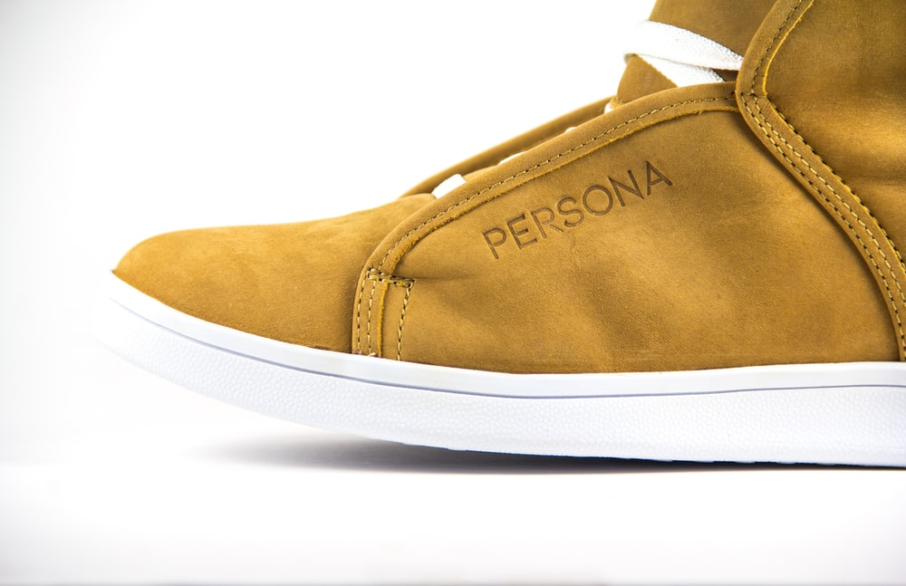 unpaired brown and white Persona suede sneaker on white surface