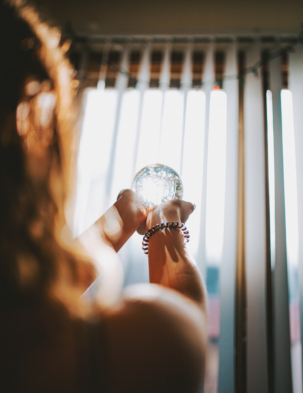 person holding clear glass snowball