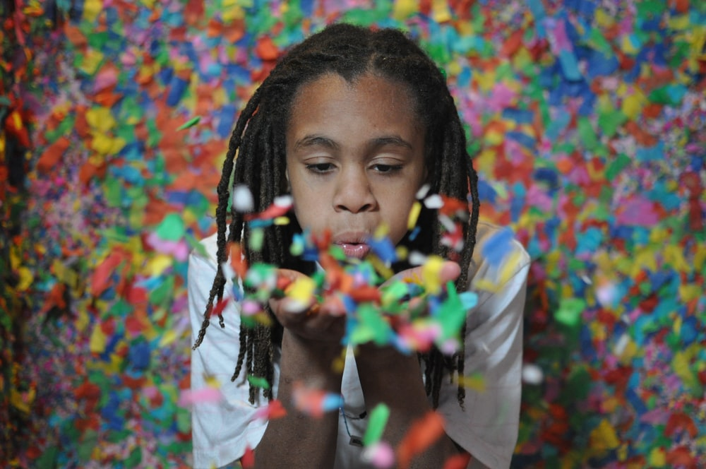 girl blowing confetti on hand