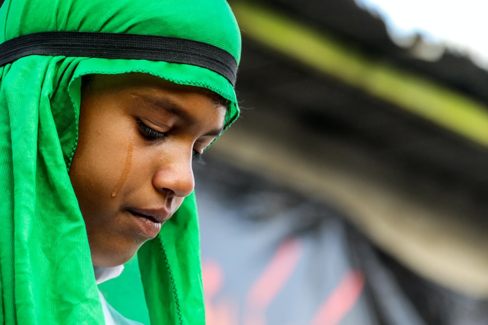 selective focus photo of crying girl wearing green hijab