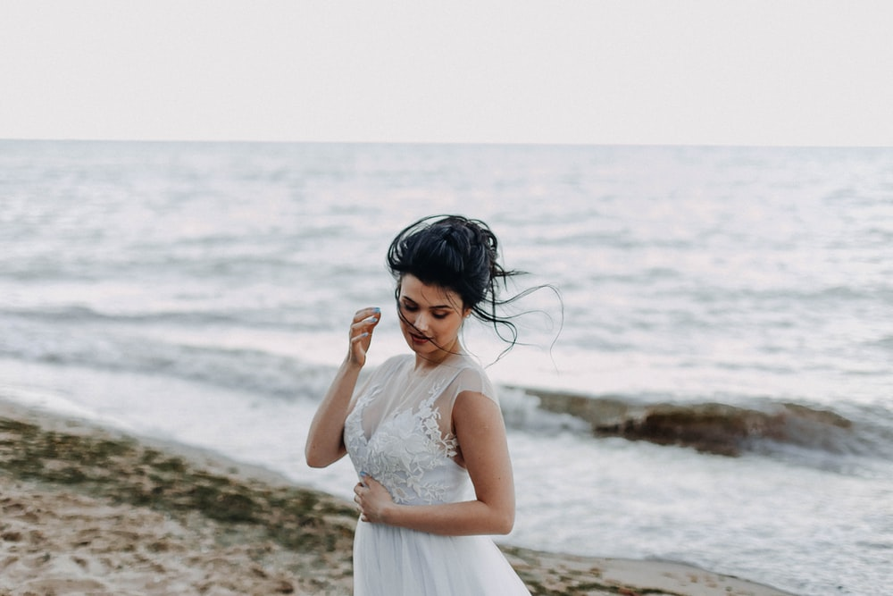 woman wearing white illusion neck lace wedding gown standing on shore during daytime