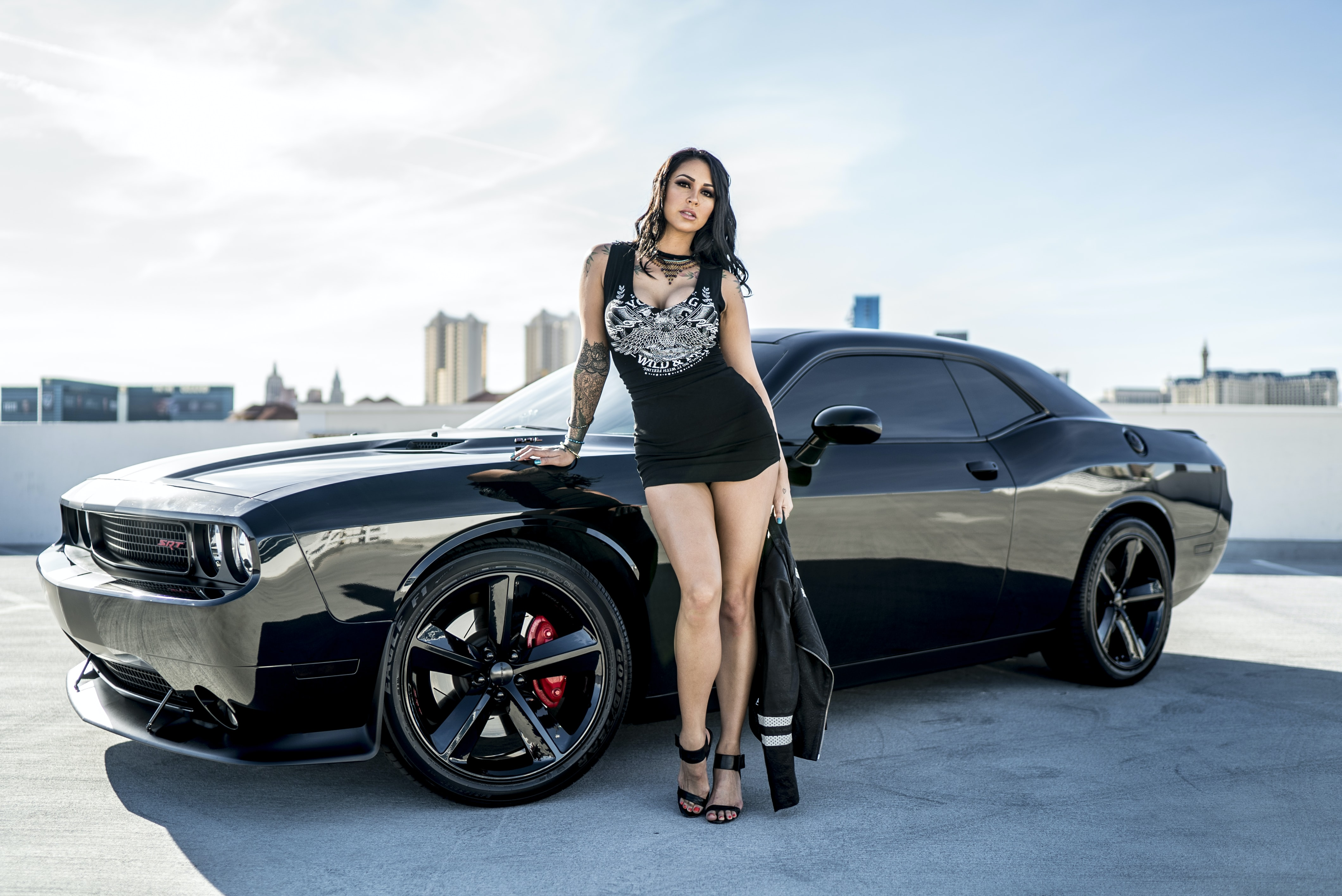 woman wearing black sleeveless dress standing in front of black Dodge Challenger