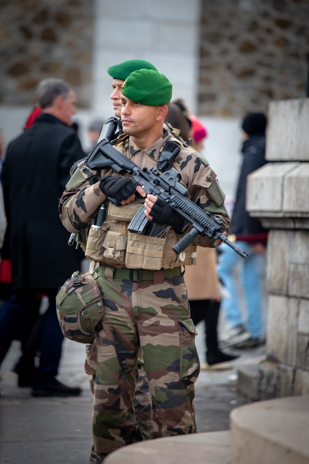 soldier with rifle stands guard in front of building