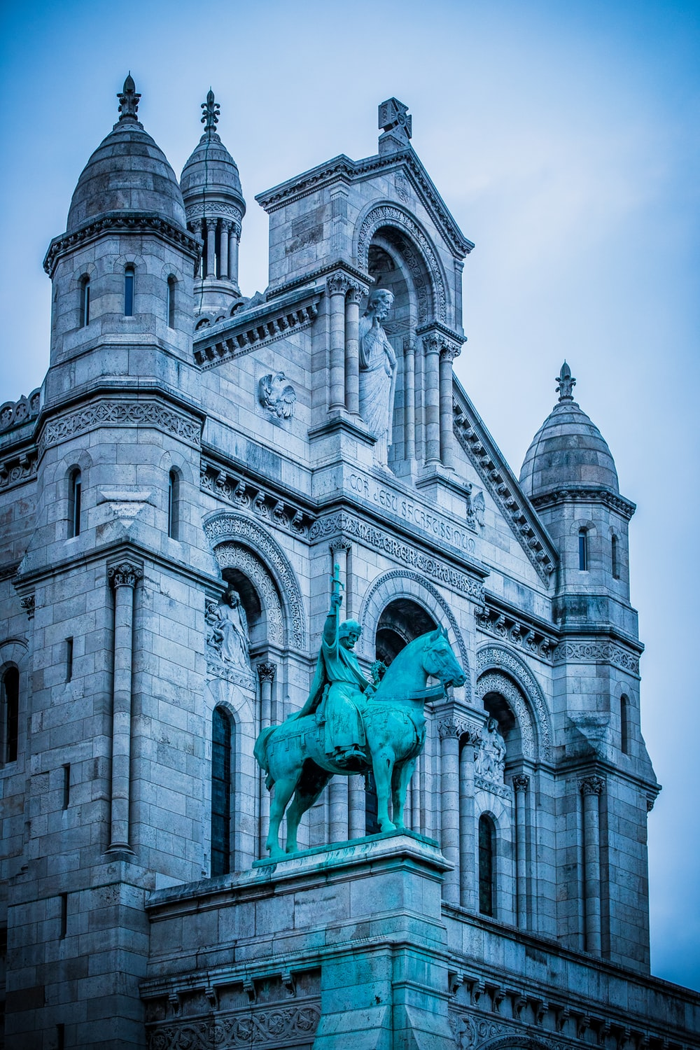 blue man on horse statue in front of cathedral