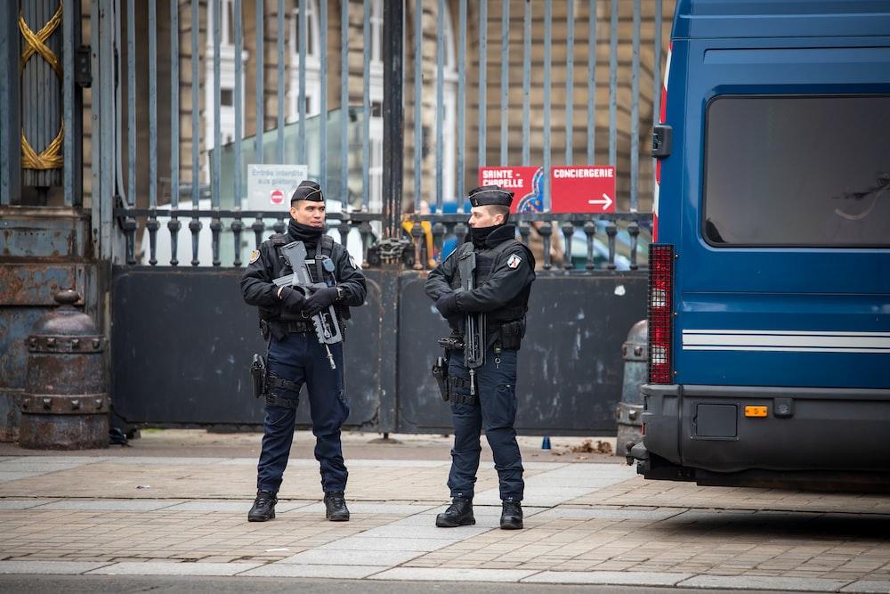 man holding black assault rifle standing on street