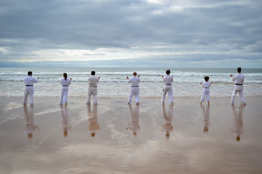 7 persons stands on beach facing sea