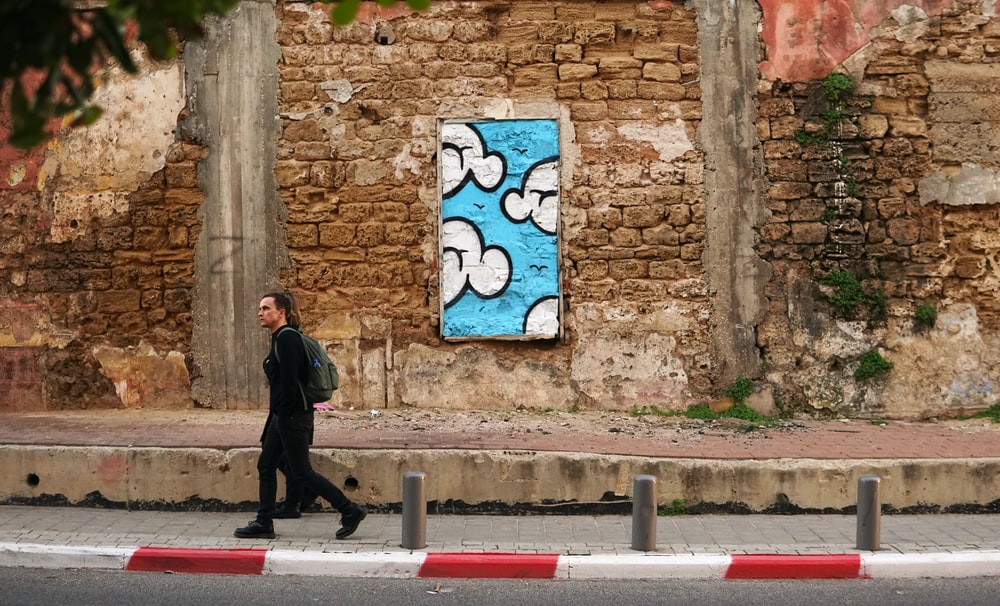 woman in black walks beside brown brick wall