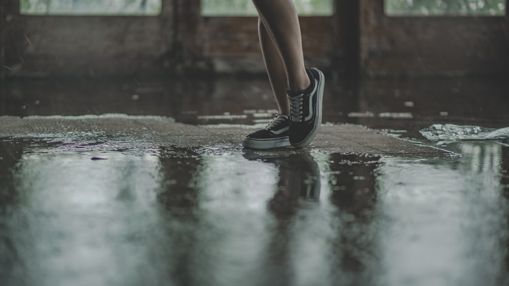 person with black Vans sneakers walking on wet pavement