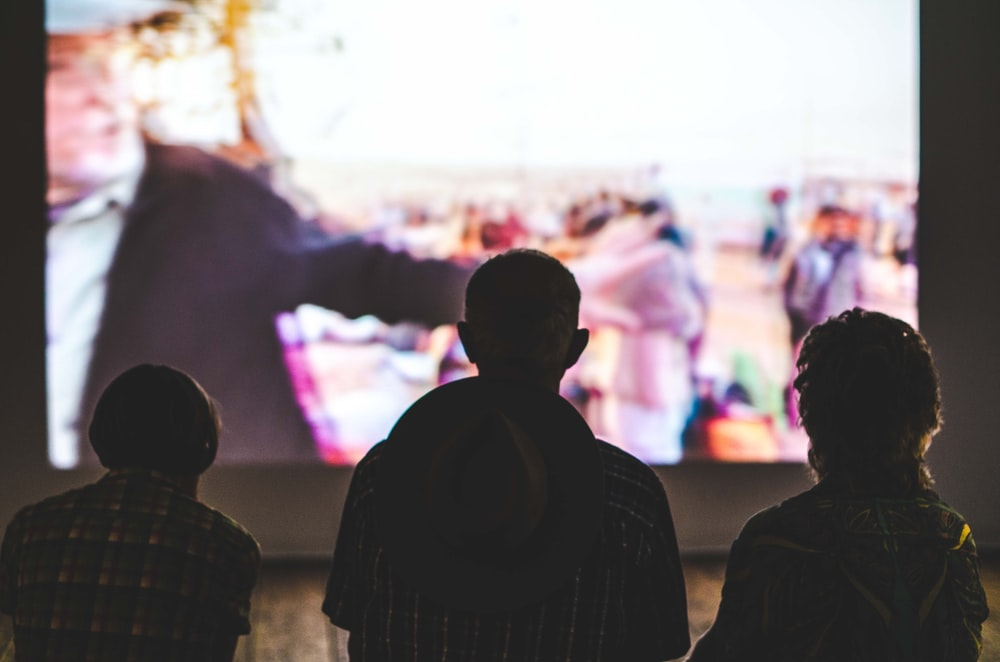 silhouette of 3 people watching show on TV
