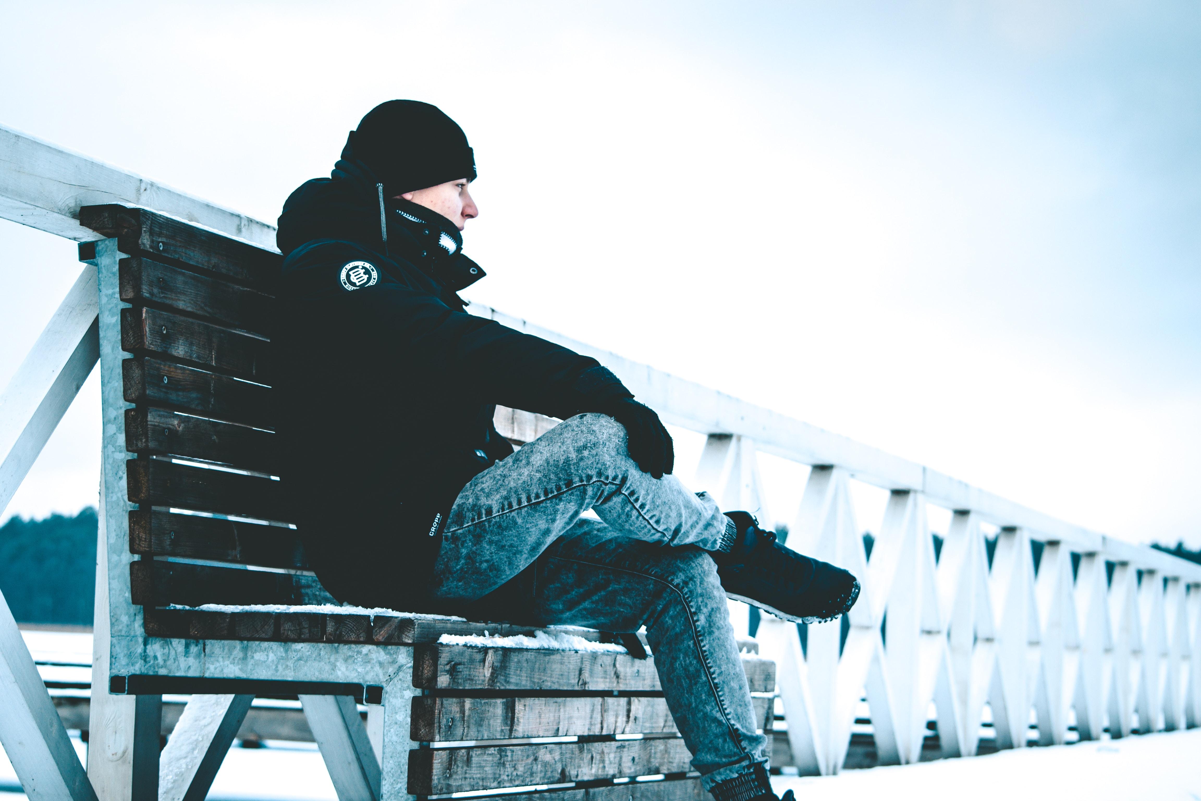 man in black jacket sits on bench beside white railing