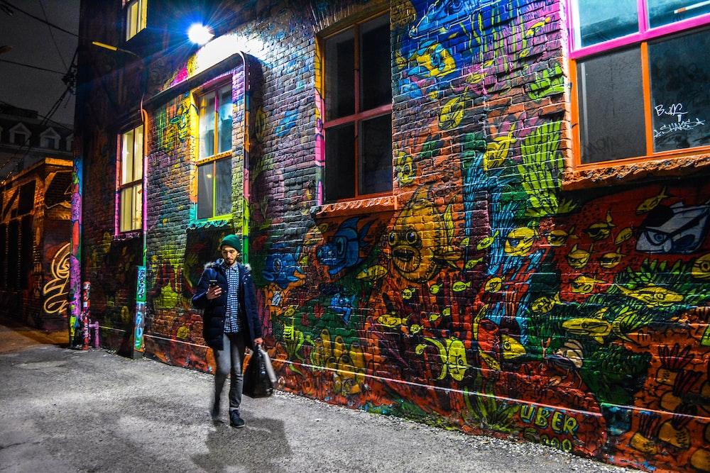 man in blue blazer walks beside confetti painted wall