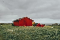 red barn in middle of grass field during daytime