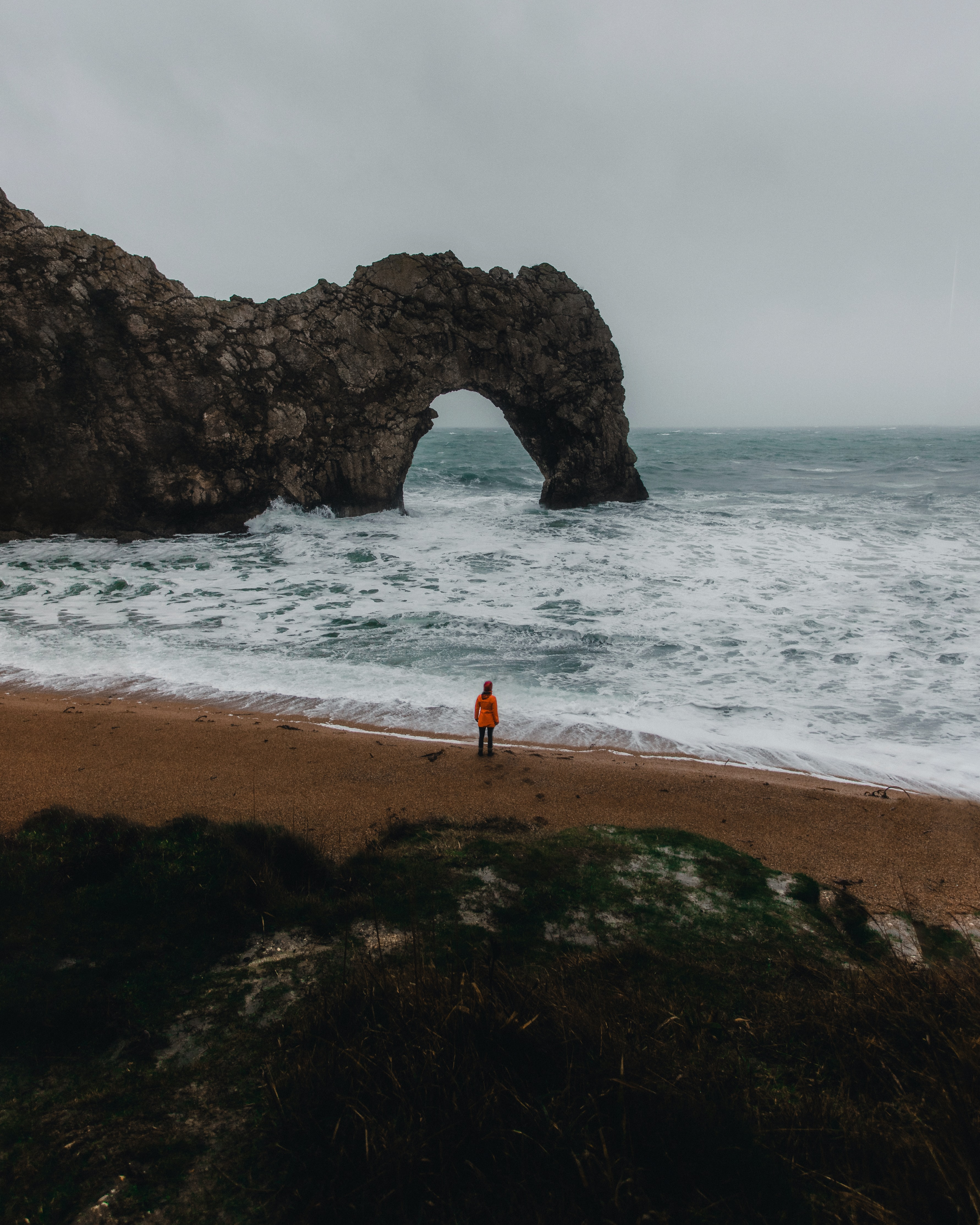 person in orange hoodie stands in front of beach