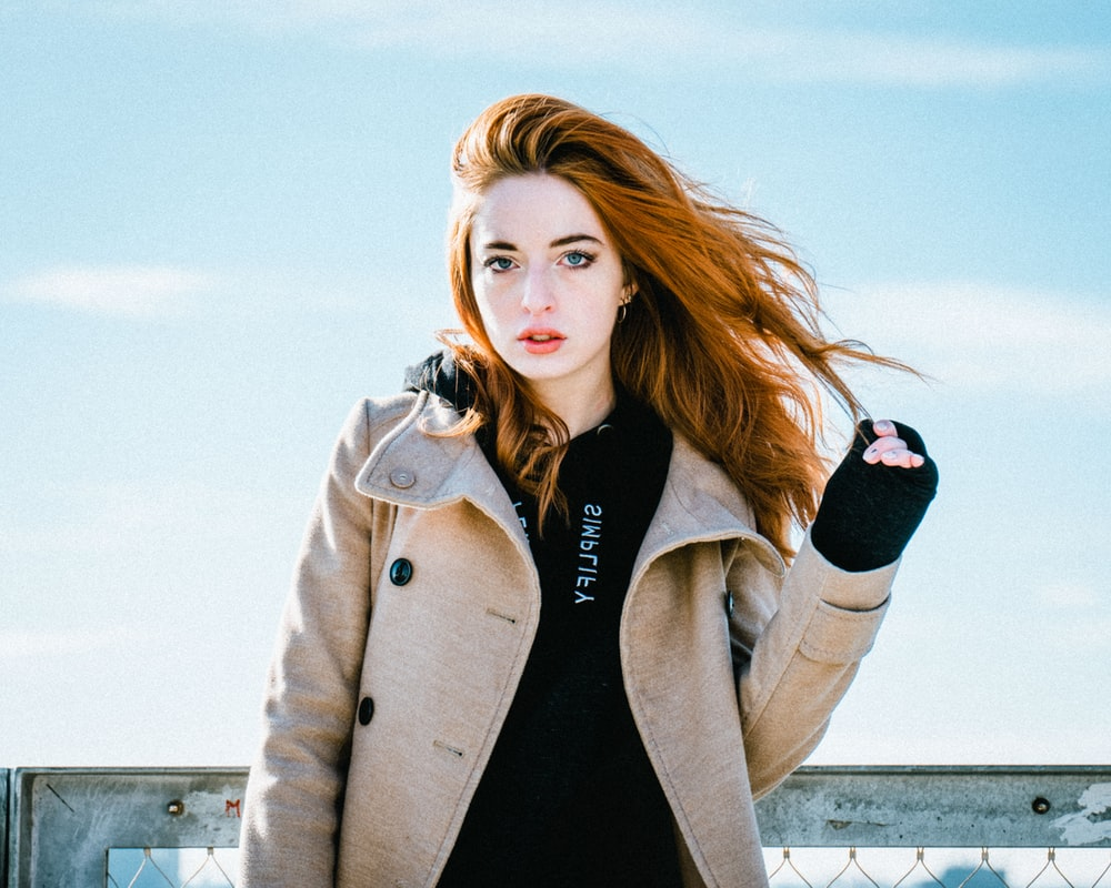 woman wearing brown jacket holding her hair